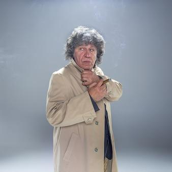灰色のスタジオで探偵またはマフィアのボスとして葉巻を持つシニア男