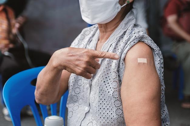 코로나바이러스 covid 예방 접종을 하러 간 후 붕대로 어깨를 가리키는 수석 여성