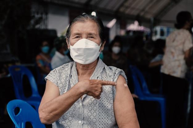 수석 여성은 붕대로 어깨를 가리키는 코로나바이러스 covid 예방 접종을 하러 갔다