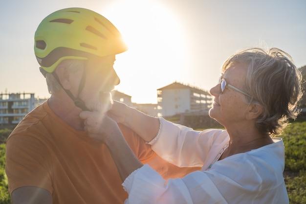 Старшая женщина ухаживает за своим мужем-велосипедистом, надевая его шлем. яркий закатный свет