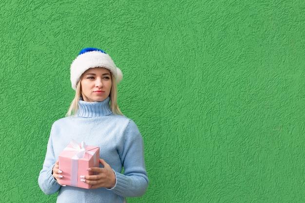 Серьезная девочка в новогодней шапке с подарком