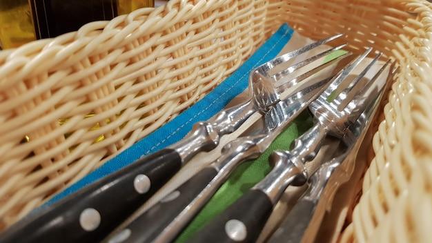 Обслуживаемый столик в ресторане. вилка, нож в коричнево-желтом плетеном пенале.