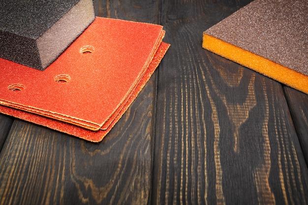 Набор абразивных инструментов и коричневой наждачной бумаги на черных старинных деревянных досках