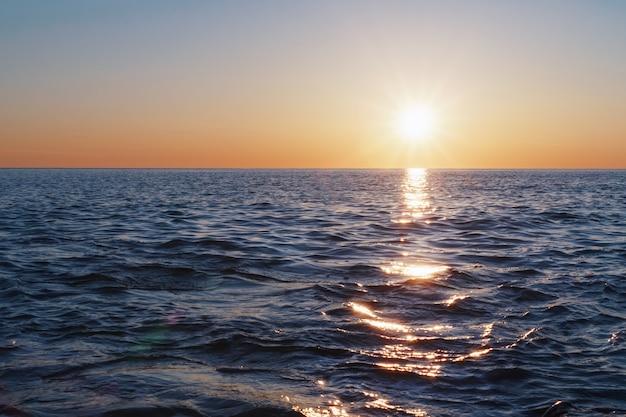 夕日は地平線の海に沈み、光の軌跡と海の反射があります。