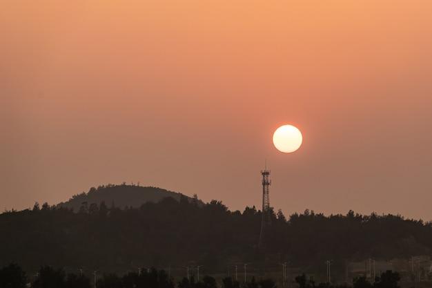 Заходящее солнце над телекоммуникационной вышкой на горе.