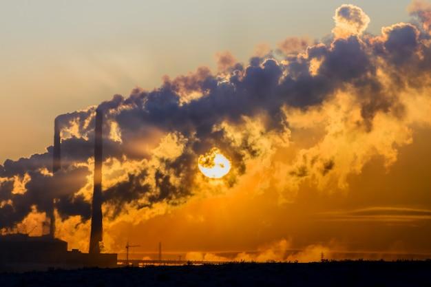 夕日は工場の煙突からの濃い煙の中を通り抜けます。極地ツンドラ、冬。