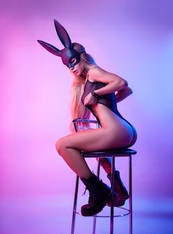 Сексуальная блондинка в маске кролика позирует на барном стуле