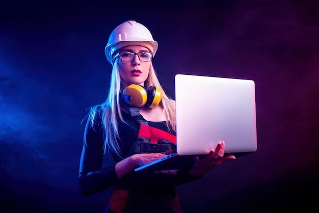 眼鏡をかけたラップトップを持つセクシーな女性建築家。ネオンの光の中で