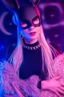 Сексуальная девушка в боди и шубе с маской кролика в неоновом свете Premium Фотографии