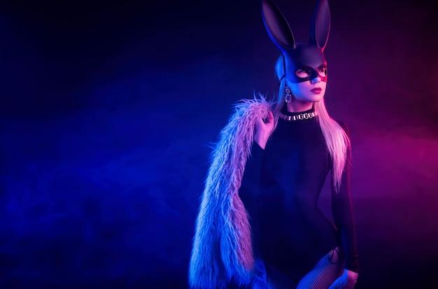 Сексуальная девушка в боди и шубе с маской кролика в неоновом свете