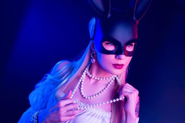Сексуальная девушка в маске кролика в неоновом свете