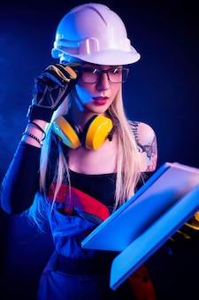 青写真を保持し、ヘルメットをかぶったセクシーな女性建築家。ネオンの光の中で