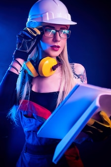 Сексуальная женщина-архитектор, держащая чертежи и носящая шлем. в неоновом свете