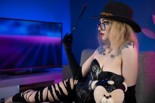 Сексуальная женщина в корсете и рваных штанах на диване с кнутом и плюшевым мишкой в аксессуарах для бдсм