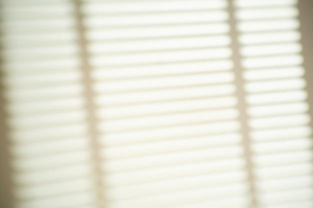 明るい光と晴れた天候の白い壁の窓のブラインドからの影。写真のシャドウオーバーレイ効果。