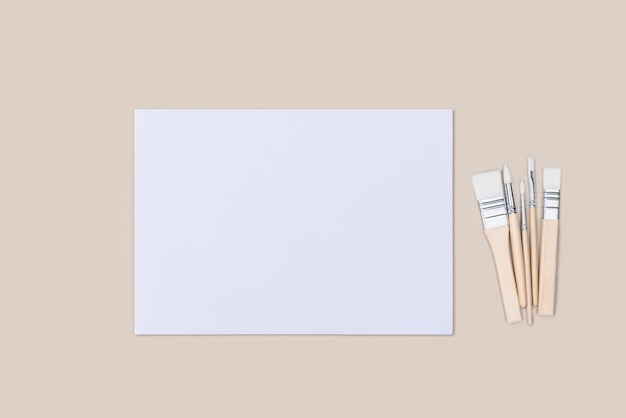 Лист чистый белый, а кисти на бежевом фоне с местом для копирования. макет, макет, верстка.