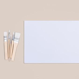 시트는 순수한 흰색이고 페인트 브러시는 복사 할 장소가있는 베이지 색 배경에 있습니다.