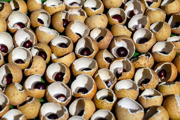 タイのフルーツリュウガンの殻と骨。リュウガンの皮の殻と穀物の背景。タイのエキゾチックなフルーツ、クローズアップ
