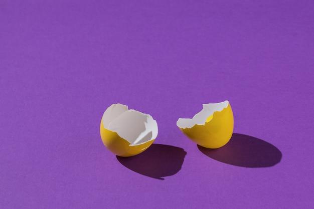 Скорлупа ярко-желтого яйца на фиолетовом фоне.
