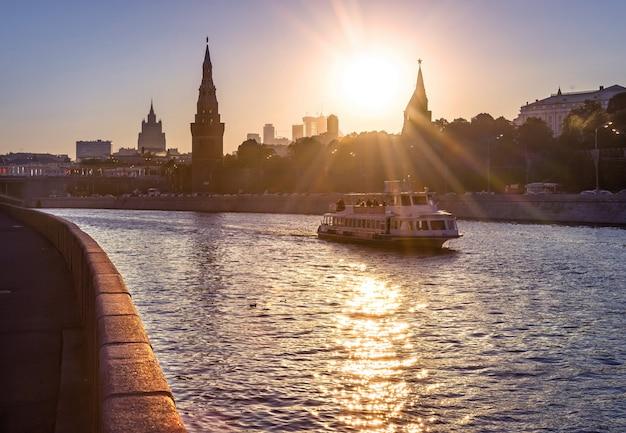 船はモスクワのクレムリンの壁の近くのモスクワ川に沿って航行しています