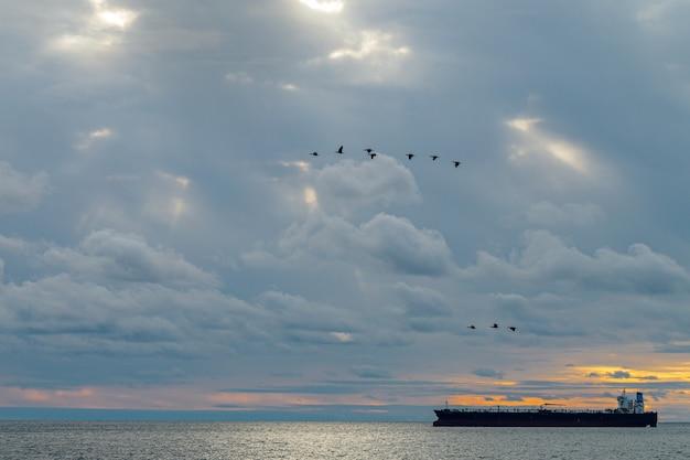 배는 아름다운 흐린 하늘을 배경으로 바다를 항해합니다.