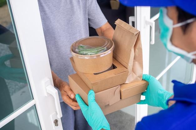 배송 업체는 마스크와 장갑을 착용하여 구매자에게 음식을 제공합니다.