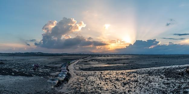 夕暮れの浅瀬、薄黄色の光と黒い土地