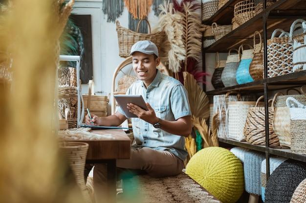 工芸品店に座ってデジタルタブレットを使いながら、店主がペンでメモする