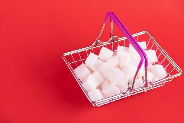 ショッピングカートは、赤い背景に洗練された砂糖の立方体でいっぱいです。スペースをコピーします。