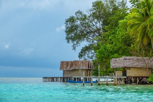 Берег небольшого острова в индонезии. два соломенных домика на сваях. пышная тропическая растительность