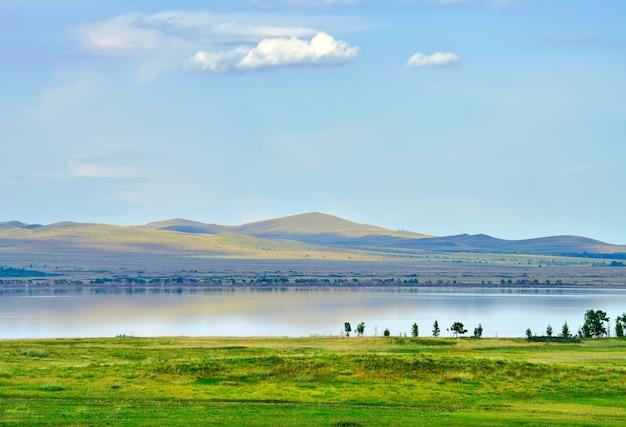 Берег степного водоема среди синих холмов летом под белым облаком в голубом небе. сибирь, россия