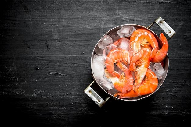 黒い黒板に氷を入れた鍋のエビ