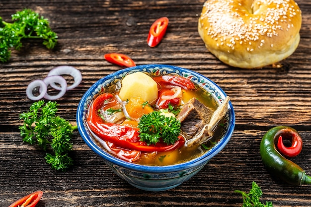 オリエンタルオーナメント、ウズベキスタンのオリエンタル料理が入ったプレートのシュルパスープ。ウズベキスタン料理。食品レシピの背景。