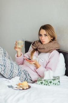 病気の不幸な若い女性は熱いお茶と一緒にベッドに横たわっています