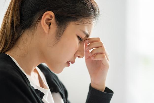 病気の女性は頭痛がして、ベッドの上の彼女の鼻に手を置いた。