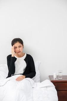 病気の女性は頭痛があり、手はベッドの上の彼女の頭に触れました。