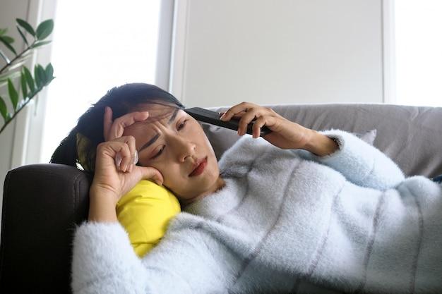 소파에 누워있는 아픈 여자는 전화로 나쁜 소식을들은 후 불안한 표정, 실망감 및 슬픔을 겪었습니다.