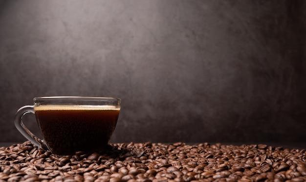 コーヒーカップと黒コーヒー豆のグループの側面図が背景です。濃い黒のエスプレッソ、コーヒーの背景、テクスチャーの根拠