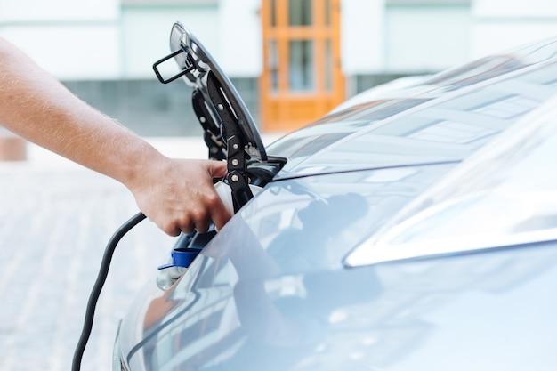 Вид сбоку аккуратной мужской руки, держащей белую электрическую насадку и заряжающей электромобиль посреди улицы Premium Фотографии