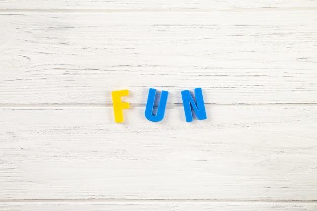 기호, 흰색 나무 배경에 재미라는 단어, 위쪽 전망. 아이들은 플라스틱 글자를 색칠했습니다.