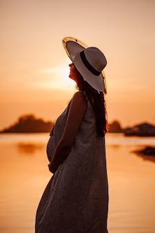 日没時の妊婦のシルエットを持っている麦わら帽子をかぶった若い女性のシルエット..。