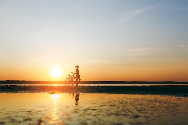 따뜻한 여름날 해질녘 물 속에서 자전거 옆에 서 있는 양복을 입은 스포티한 소녀의 실루엣. 피트니스 개념입니다.
