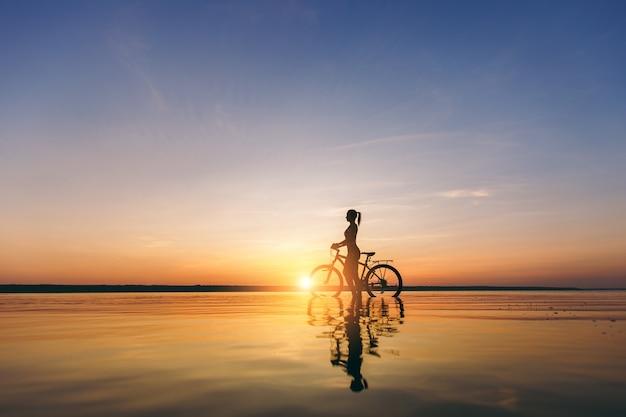 Силуэт спортивной девушки в костюме, которая сидит на велосипеде в воде на закате в теплый летний день. концепция фитнеса.