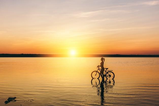 暖かい夏の日の日没時に水中で自転車に座っているスーツを着たスポーティな女の子のシルエット。フィットネスのコンセプト。