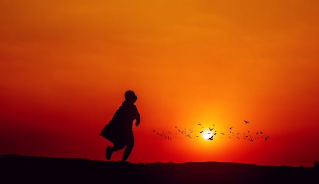 슈퍼 히어로의 실루엣은 결단력과 결단력으로 앞으로 돌진합니다. 백그라운드에서 태양과 조깅, 실루엣 개념 및 저녁 달리기