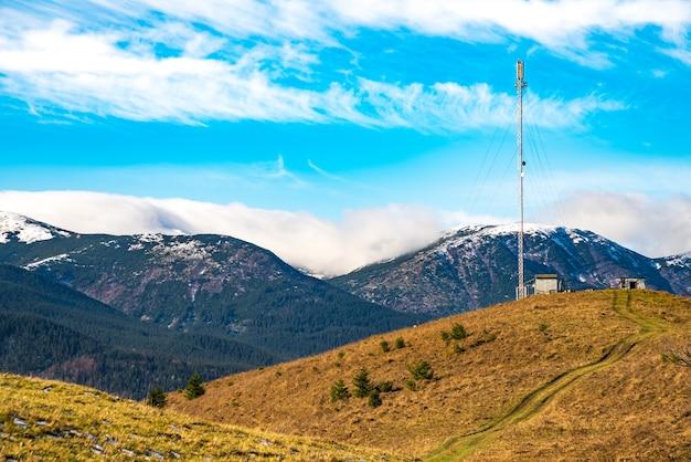 흐릿한 밝은 흰 구름과 놀랍도록 아름다운 푸른 하늘을 배경으로 통신 타워의 실루엣
