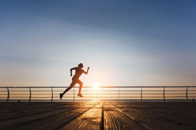Силуэт молодой красивой спортивной девушки с длинными светлыми волосами в черной одежде, бегущей на восходе солнца над морем