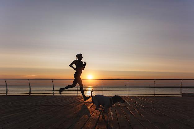 彼女の犬と一緒に海の上を夜明けに実行するヘッドフォンで長いブロンドの髪を持つ若い美しい運動少女のシルエット