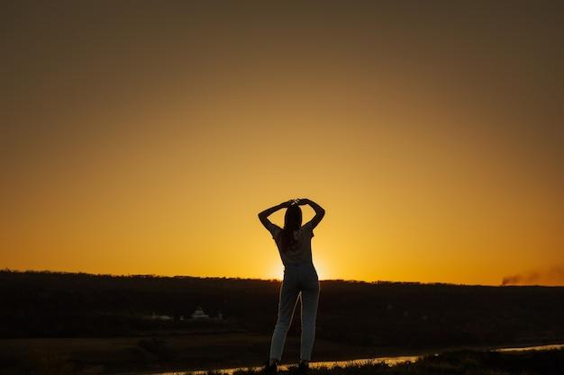 遠くに夕日を見ている若い女性のシルエット。