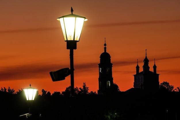 빛나는 금빛 밝은 주황색 하늘을 배경으로 정교회의 실루엣